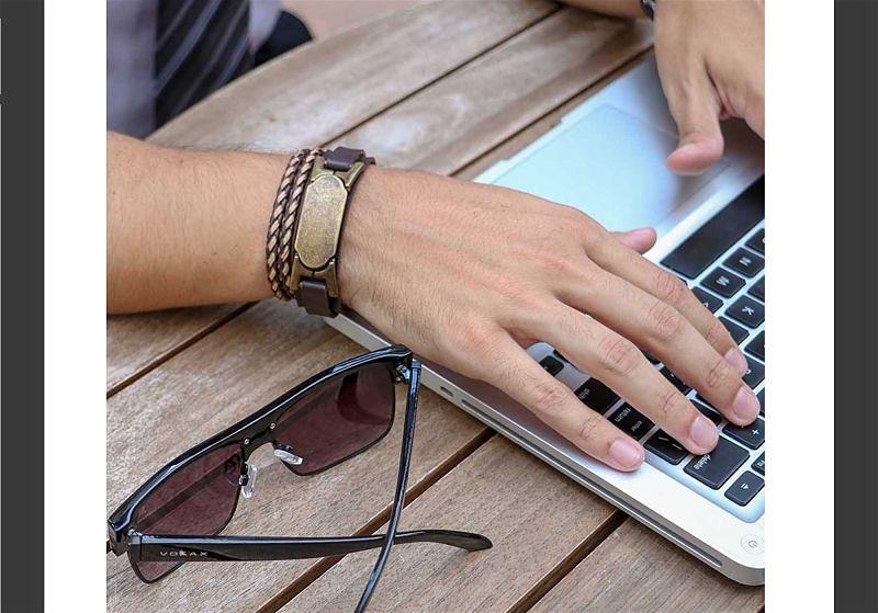 Imagem em destaque de homem usando pulseira enquanto utiliza o notebook