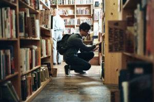 Homem escolhendo livro para ler