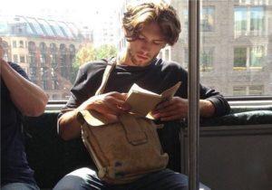 homem charmoso lendo livros no metrô de NY