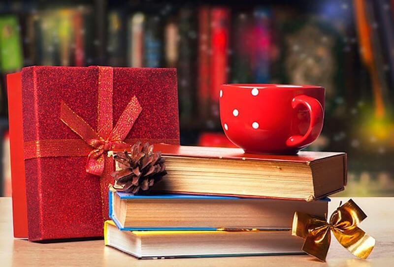 imagem de pilha de livros ao lado de pacote de presente