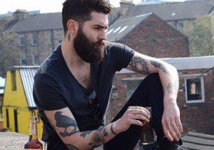 modelo masculino com barba sentado em paisagem industrial