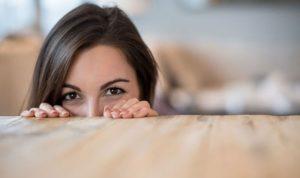 mulher tímida mostrando somente os olhos sob a mesa