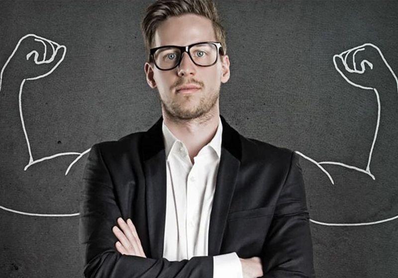 homem de braços cruzados com desenho de braços musculosos ao fundo