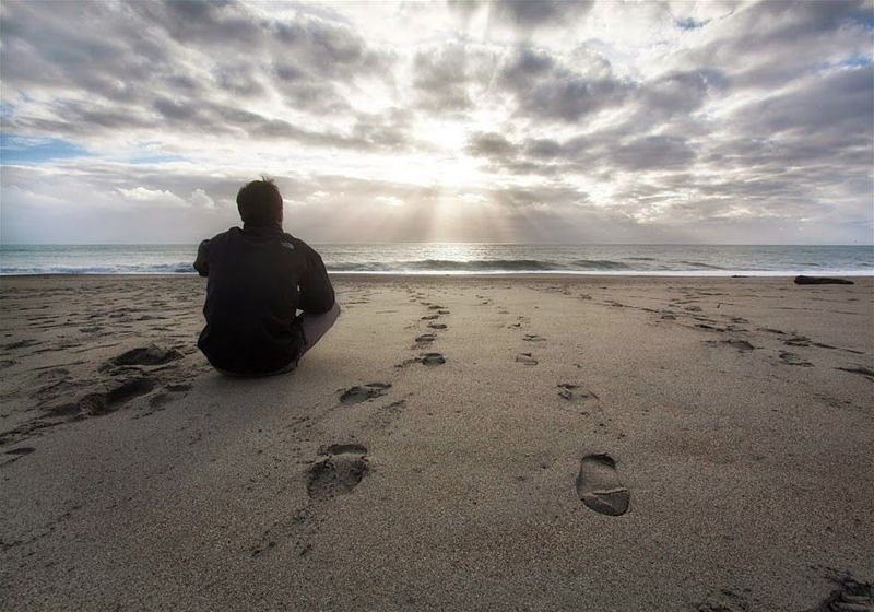 Imagem de um rapaz sentado na beira da praia