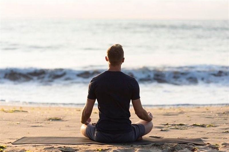 Imagem de um rapaz sentado na beira da praia olhando o mar