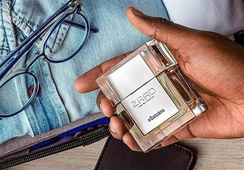Imagem focada da mão de um homem segurando o perfume Zaad do O Boticário