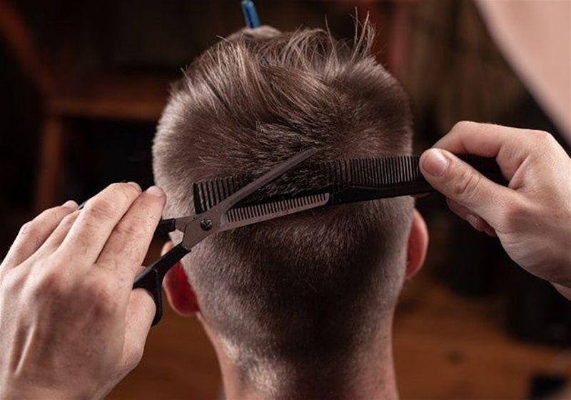 Imagem aproximada de um cabelereiro realizando um corte de cabelo em um modelo masculino
