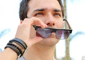 Imagem aproximada do rosto de um modelo masculino usando óculos escuros e acessórios no braço