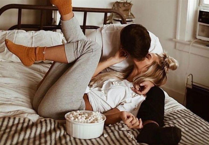Imagem de um casal de namorados se beijando em cima de uma cama