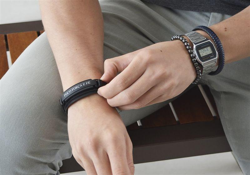 Imagem em destaque dos pulsos de um modelo masculino, que usa pulseiras e um relógio