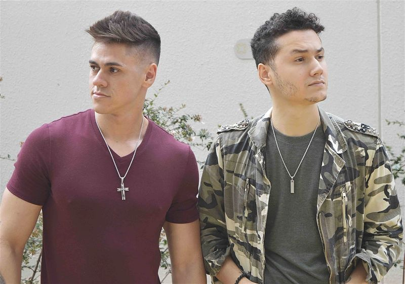 Imagem de dois modelos masculinos usando uma camiseta lisa e colares a mostra
