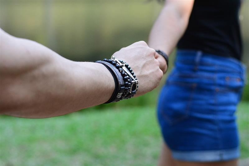 Imagem aproximada de um homem segurando a mão de uma mulher