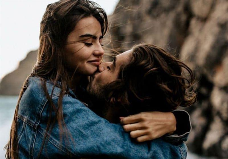 Imagem de um casal de namorados se abraçando ao ar livre