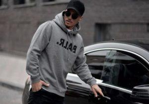 Imagem de modelo masculino, abrindo a porta de um carro, usando uma blusa de moletom