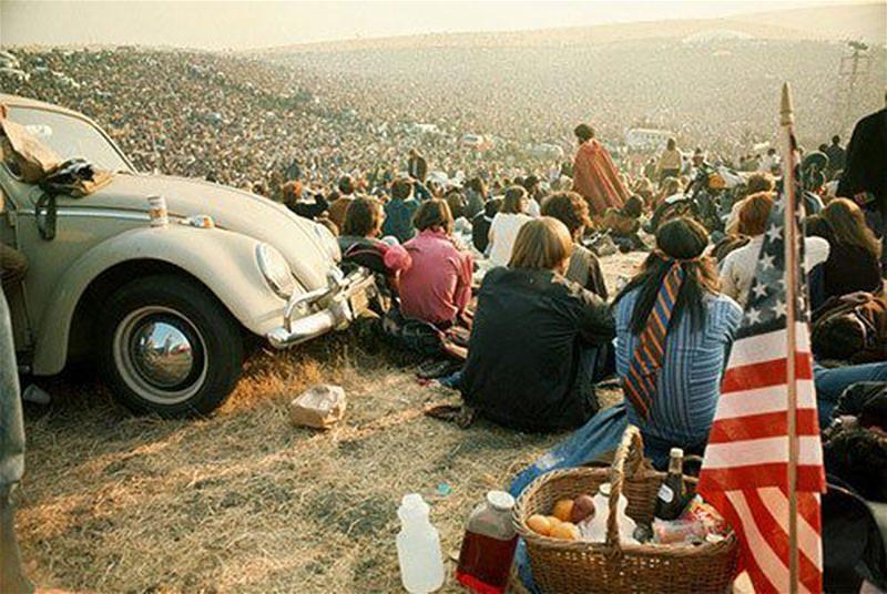 Imagem de jovens sentados na grama em um festival de música nos anos 60