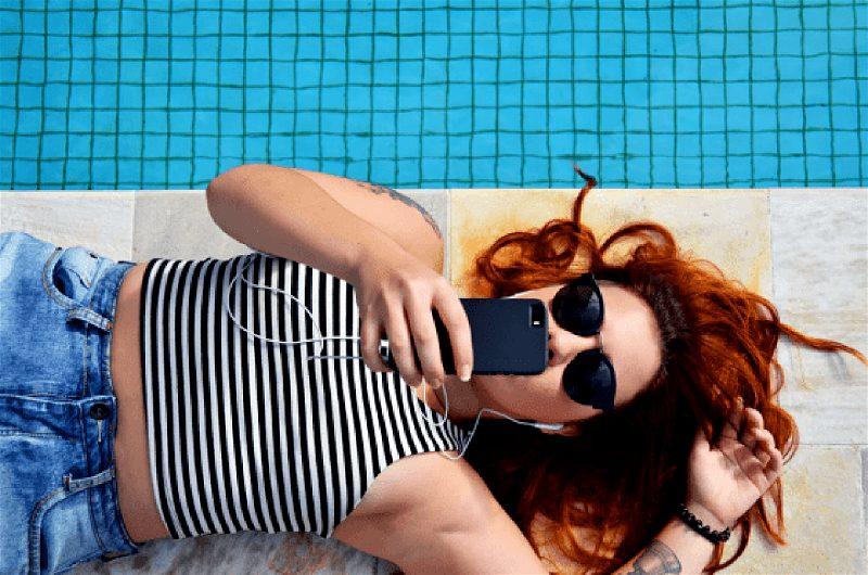 Imagem de uma moça deitada na beira da piscina conversando com alguém por meio do smartphone