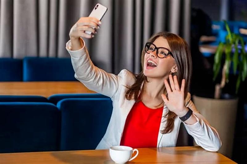 Imagem de uma mulher tirando uma selfie com o smartphone