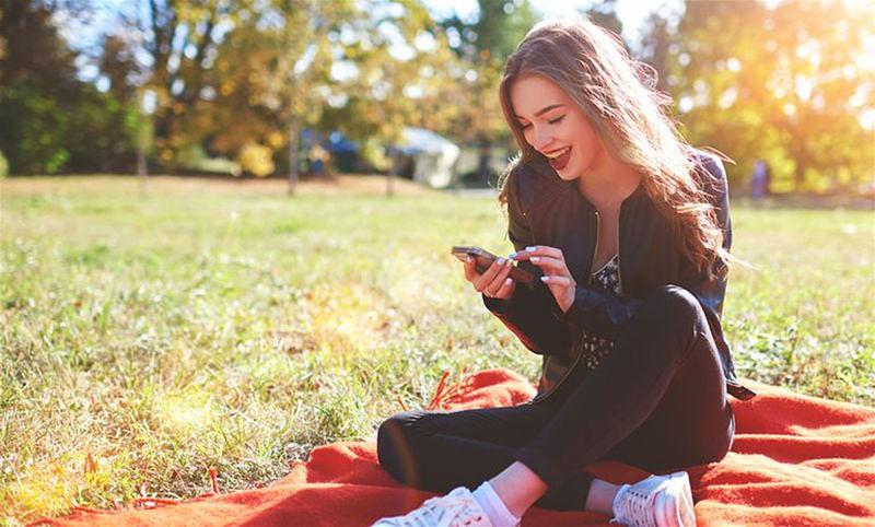 Imagem de uma mulher sentada na grama usando um smartphone